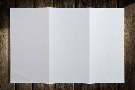 Folded duplicating paper on wood background photo
