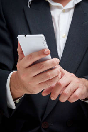 cellular telephone: Businessman using white smart phone