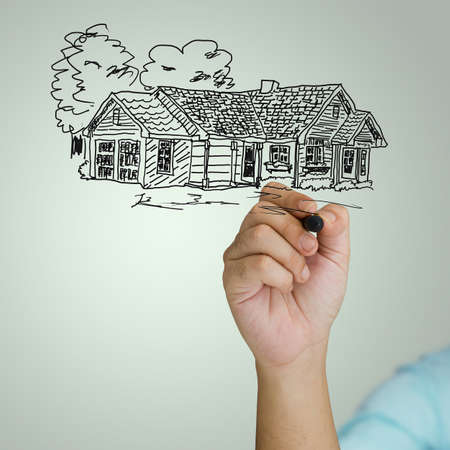 Hand sketching house on green background photo