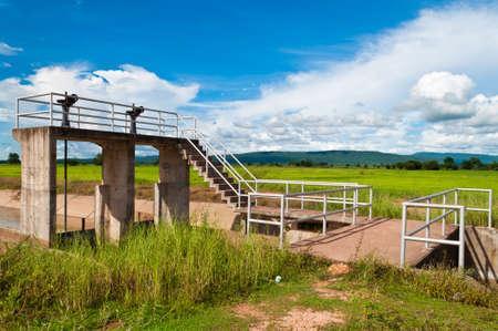sluice: Sluice on irrigation canal in farmland Stock Photo