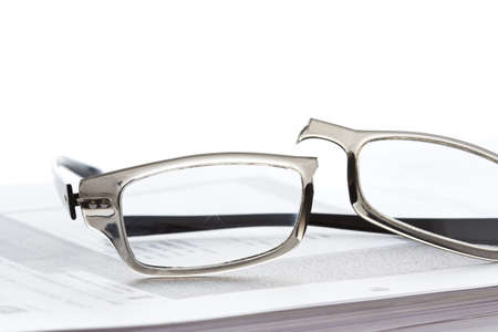 Broken eyeglasses on document papers 写真素材