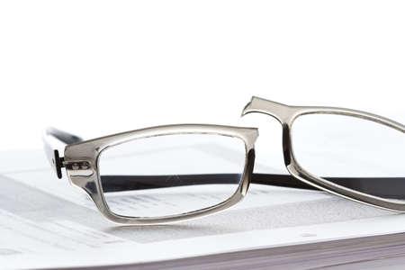 Broken eyeglasses on document papers Stock Photo