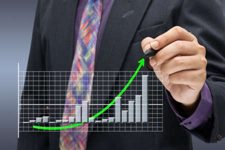Businessman writing arrow on success graph photo