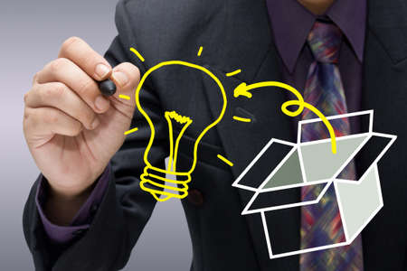 Businessman drawing a light bulb outside the box