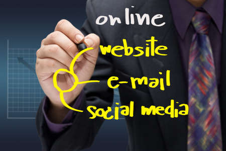 Businessman writing a trend of online channels for business photo
