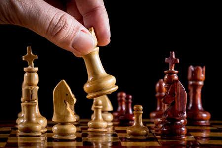 jugando ajedrez: Mano jugando al ajedrez de madera en fondo negro
