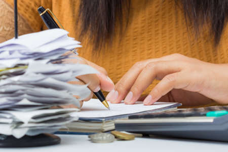 taxpayer: Closeup woman writing paper on the desk Stock Photo