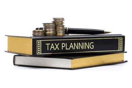 taxes: Impuesto libro de planificaci�n con monedas y pluma aislados en blanco Foto de archivo