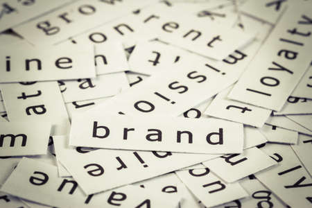topic: Brand topic in cut paper on the top of the others word Stock Photo