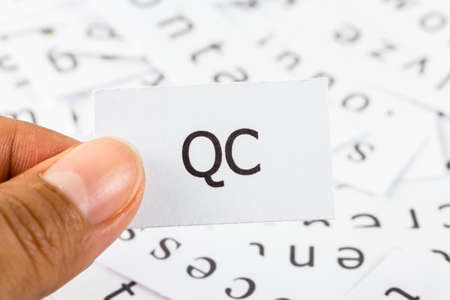 qc: QC word on paper picked by finger to see close