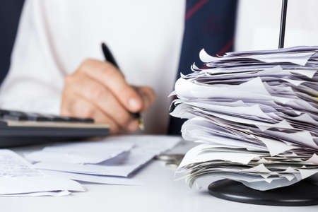 Stack of bills in paper nail with businessman calculating