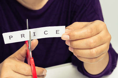 price cutting: Closeup woman cutting paper of price word Stock Photo