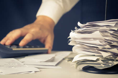 tax bills: Stack of bills in paper nail with hand calculating