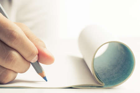 Hand going to write something on folded notebook photo