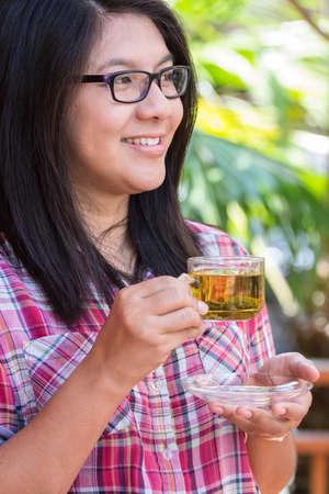 tomando refresco: Mujer asi�tica sonriente con la taza de t� en la mano