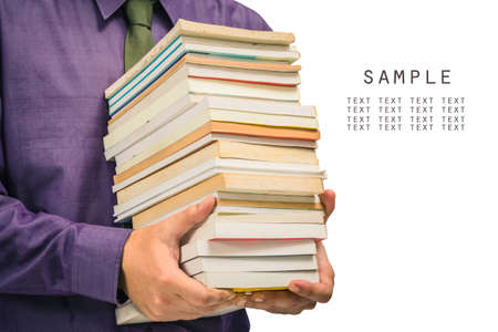 Closeup man holding a pile of used books isolated on white background photo