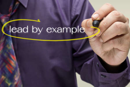 Businessman draw a circle mark on Lead By Example text photo