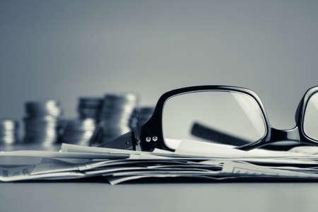 Financiële werk op het bureau in koud klankkleur (brillen, wissels en munten)