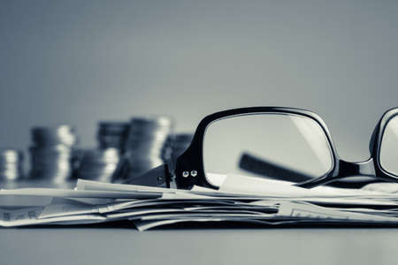 Financial work on the desk in cold tone color (eyeglasses, bills, and coins)