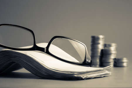 accountancy: Eyeglasses and pile of bills for accountancy calculation concept