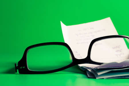 Eyeglasses and receipts on green background  (home economic or financial work concept) photo