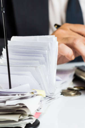 A lot of receipts in paper nail with accountant working on background photo