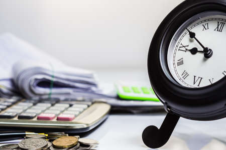 Clock on financial desk,concept of busy or working overtime photo