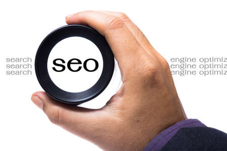 Hand holding magnifying loop to see SEO word Stock Photo - 21236933