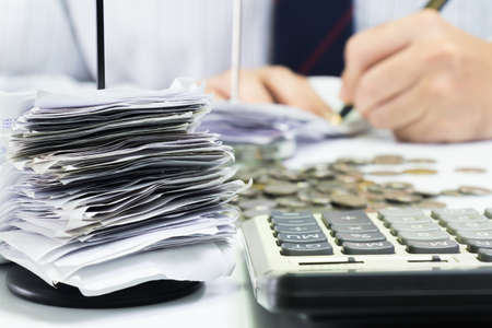 Receipts in paper nail with businessman working as background