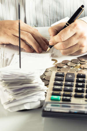 Businessman working with receipts on financial desk photo
