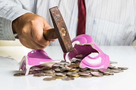Businessman smashing piggy bank with hammer photo