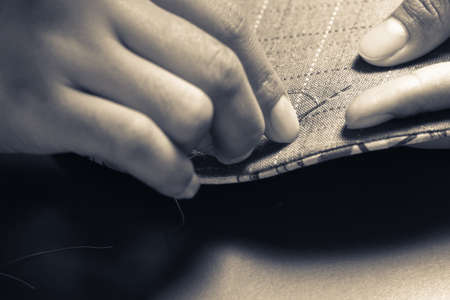 Closeup woman hand sewing quilt photo