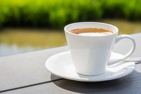 Coffee on wood bench with green field background photo