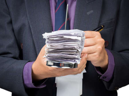 Businessman working with bills in paper nail photo
