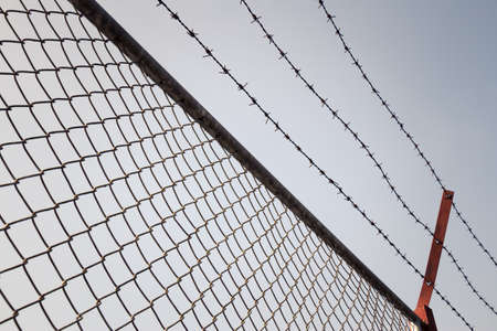 Metal mesh fence and barbed wire photo