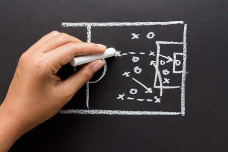 Hand drawing a soccer strategy chart with chalk photo
