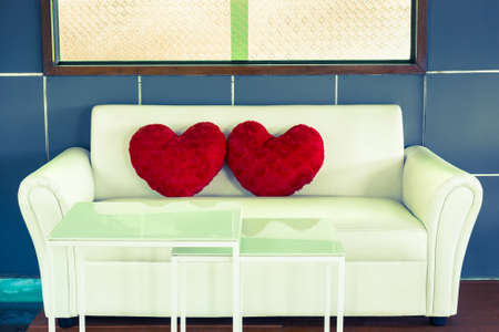 Sofa and heart pillows with green window in retro color style photo