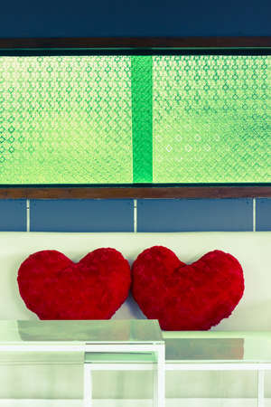 Two heart pillows on sofa with green window in retro color style photo