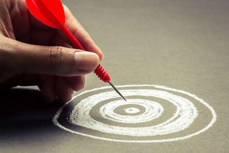 de hand gaat dart naar het centrum van schetsen dartboard