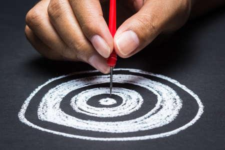 hand gaan dart in het midden van het schetsen dartbord nemen