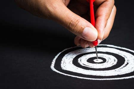 Ajuste de la meta o una planificación precisa, la mano va a tomar dardo en el centro de esbozar diana Foto de archivo