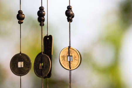 Antique Chinese coins hanged outside the house as wind chimes  for protection and good luck Stock Photo