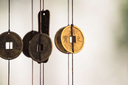 Antique Chinese coins hanged outside the house as wind chimes  for protection and good luck photo