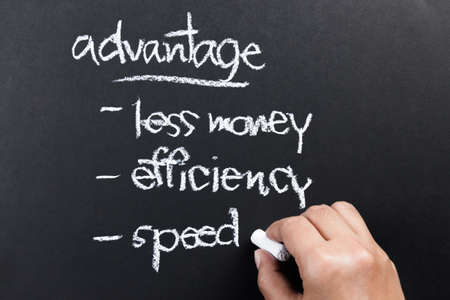 Hand writing a competitive advantage of business concept with chalk photo