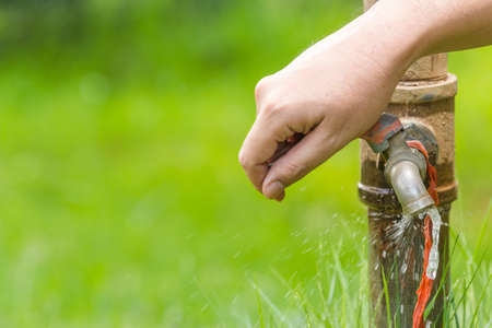 conserve: Hand  turn off running water from old faucet Stock Photo