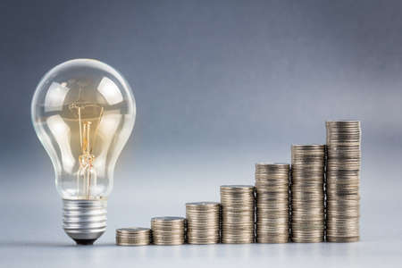 financial metaphor: Light bulb with heap of coins stairs for financial plan or business idea concept