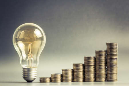財務計画やビジネス アイデアの概念のためのコイン階段のヒープと電球