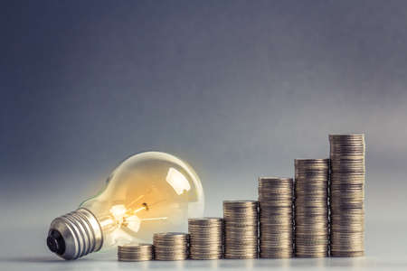 Light bulb with heap of coins stairs for financial plan or business idea concept photo
