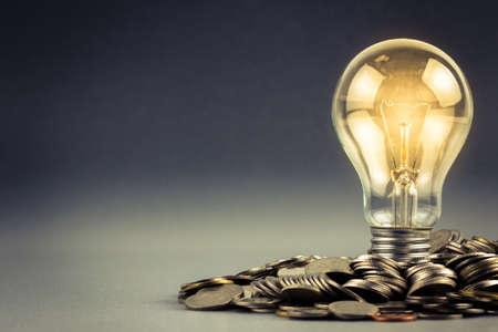 Gloeilamp en stapel van munten met een kopie ruimte
