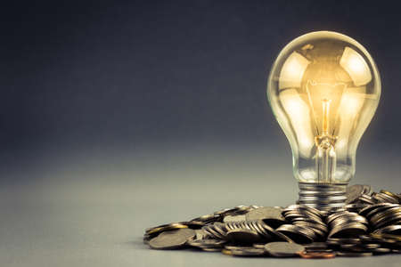 save money: Light bulb and pile of coins with copy space